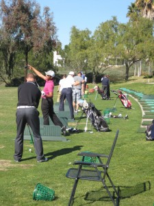 younger golfers hitting drivers on the range