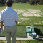 golfer begining process to his golf pre shot routine on the driving range