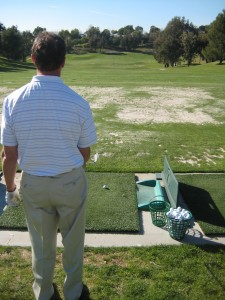 golfer begining process to his pre-shot routine on the driving range